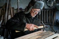 Oude hogere timmerman in grijze warme kleren in oogglazen royalty-vrije stock foto's