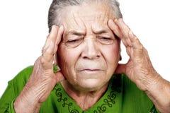 Oude hogere vrouw die migraine of hoofdpijn heeft royalty-vrije stock foto's