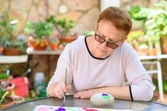Oude hogere vrouw die pret het schilderen in kunstklasse hebben openlucht stock foto