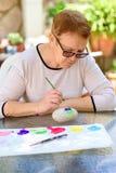 Oude hogere vrouw die pret het schilderen in kunstklasse hebben openlucht royalty-vrije stock foto's