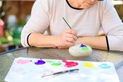 Oude hogere vrouw die pret het schilderen in kunstklasse hebben openlucht royalty-vrije stock fotografie