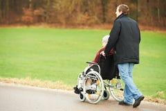 Oude hogere vrouw in rolstoel met zorgvuldige zoon Stock Afbeelding