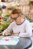 Oude hogere vrouwen die pret het schilderen in kunstklasse hebben openlucht stock foto's