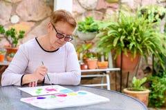 Oude hogere vrouwen die pret het schilderen in kunstklasse hebben openlucht stock afbeelding