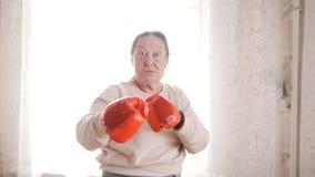 Oude hogere vrouwen die in rode handschoenen in dozen doen, die agressief grappig kijken stock afbeeldingen