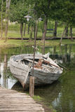 Oude houten boot in ondiepe wateren Stock Afbeeldingen