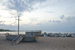Oude houten boot op een zandig strand op de steenachtige kust royalty-vrije stock foto's