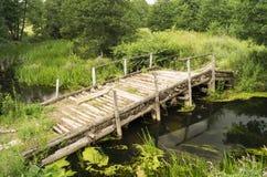 Oude houten brug door stroom stock afbeeldingen