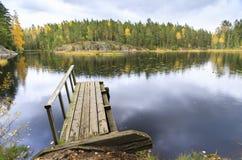 Oude houten brug in een meer in de herfst Stock Afbeelding