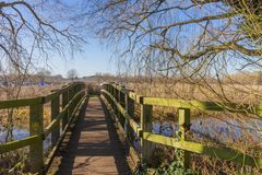 Oude houten brug over de rivier De vroege lente in Engeland royalty-vrije stock afbeelding