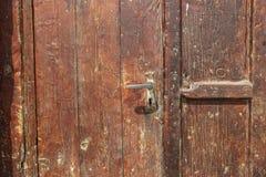 Oude houten deur donkerrode kleur en het oude fragment van het ijzerslot royalty-vrije stock afbeelding