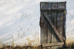 Oude houten deur in een oude steenmuur stock foto