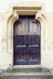 Oude houten deur met metaalknop in Prejmer versterkte kerk, Braso Stock Foto