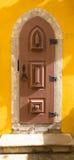 Oude houten deur met metaalscharnieren en slot op de gele muur Stock Fotografie