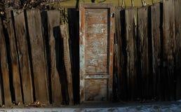 Oude houten deur met schil blauwe verf en kromme houten omheining Stock Fotografie