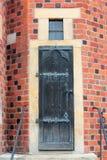 Oude houten deur met smeedijzerdetails in de bakstenen muur Wroclaw, Polen royalty-vrije stock afbeelding