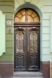 Oude houten deuren met gebrandschilderd glasvensters, gesmede grills en ornamenten Stock Foto's
