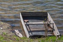 Oude houten die boot aan de bank van het meer wordt vastgelegd royalty-vrije stock fotografie
