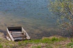 Oude houten die boot aan de bank van het meer wordt vastgelegd royalty-vrije stock afbeelding