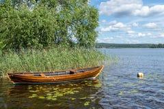 Oude houten die boot aan een boei op een zonnige de zomerdag wordt gebonden stock foto's