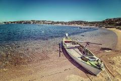 Oude houten die boot op het zand wordt gebonden stock foto's