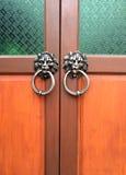 Oude houten die deur met een leeuwhoofd als kloppers wordt verfraaid Stock Afbeelding