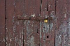 Oude houten die deuren met metaal geel slot worden gesloten Nieuw geel slot op oude bruine deuren stock foto