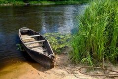 Oude houten die het roeien boot met ketting en hangslot bij groene samenvatting wordt gebonden stock fotografie