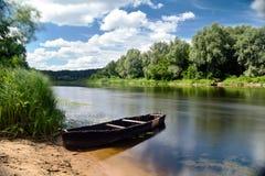 Oude houten die het roeien vissersbootveerboot aan zandige strandsom wordt geketend Stock Afbeeldingen
