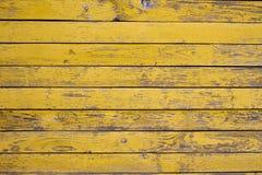 Oude houten die oppervlakte met vlokkige gele verf wordt behandeld royalty-vrije stock fotografie
