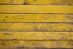 Oude houten die oppervlakte met vlokkige gele verf wordt behandeld royalty-vrije stock foto