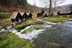 Oude houten die watermolennen op een snel stromend rivierkanaal worden voortgebouwd in het populaire oude dorp Stock Foto