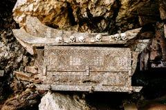Oude houten doodskist met schedels en beenderen dichtbij op een rots Hangende doodskisten, graven Traditionele begrafenissenplaat Stock Afbeelding