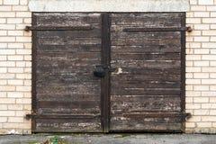 Oude houten garagedeur met hangslot stock fotografie