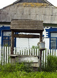 Oude houten goed dichtbij huis in dorp Oude houten goed met emmer het hangen op ketting Stock Afbeelding