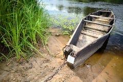 Oude houten het roeien boot bij groene de zomerbank bij middag op Neman riv stock foto's