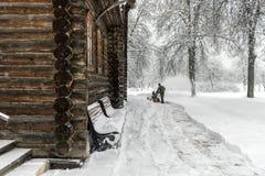 Oude houten kerk Het landschap van de winter Een arbeider verwijdert Sn stock fotografie