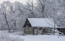 Oude houten loods tijdens een sneeuwval stock fotografie