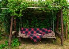 Oude houten schommeling in de groene tuin Stock Foto's