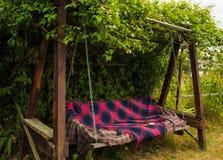Oude houten schommeling in de groene tuin Stock Afbeeldingen