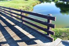 Oude houten uitstekende brug die een mooi meer overzien stock afbeelding