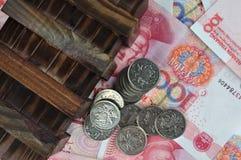 Oude houten vakje en muntstukken op geldnota's Royalty-vrije Stock Afbeelding