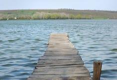 Oude houten voetgangersbrug over het meer. Royalty-vrije Stock Foto's