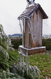 Oude Houten Vogelvoeder met ijskegels die van post hangen stock fotografie