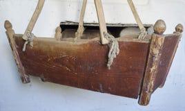 Oude houten wieg in dorpshuis stock fotografie