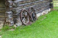 Oude houten wielen van kar op schuurmuur Stock Afbeeldingen