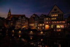 Oude huizen met lichtgevende vensters in de avond stock afbeeldingen