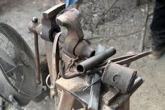 Oude hulpmiddelen en bankschroef in smidsworkshop stock foto's