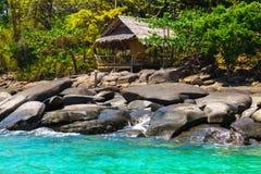 Oude hut op steenstrand van blauwe tropische overzees Stock Afbeeldingen
