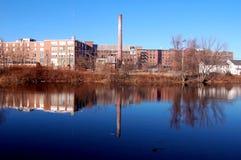 Oude industriële fabriek door rivier stock foto's